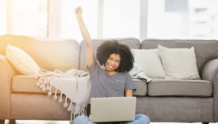 Shot of an attractive young woman using a laptop and cheering at home