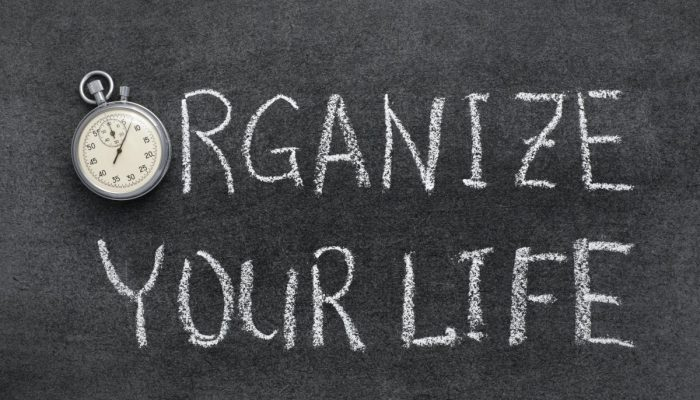 organize your life phrase handwritten on chalkboard with vintage precise stopwatch used instead of O